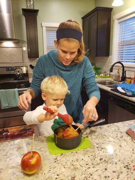 Helping put the caramel on apples