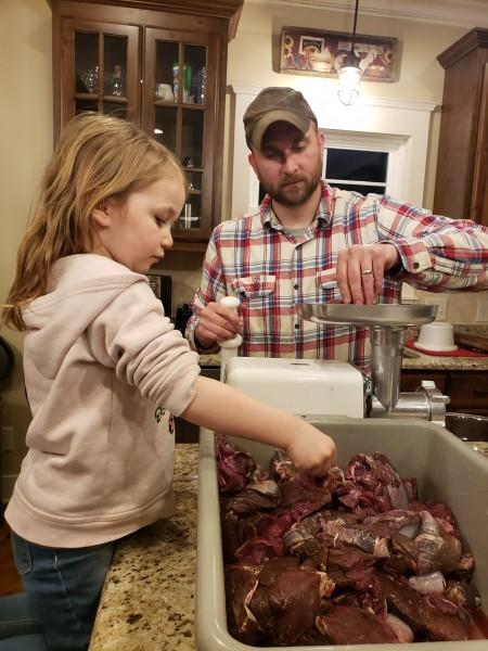 Grinding deer meat.