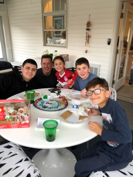 Patrick building gingerbread houses with his nephews and nieces