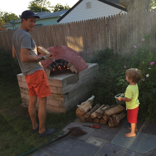 David shows a little friend the ins and outs of pizza making in the cob oven we built.