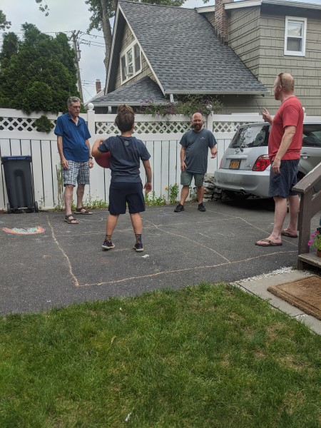 Our family playing four square in our driveway