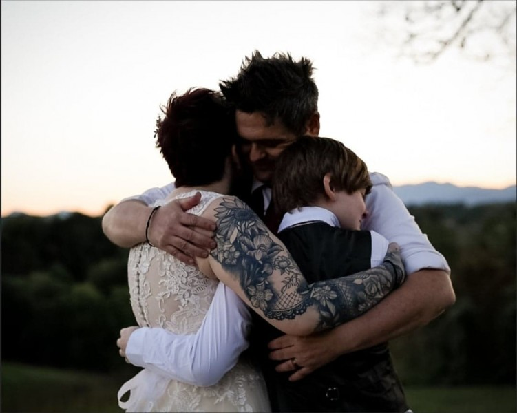 paul, heather and parker hugging at wedding.