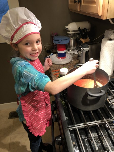 Lydia learning to make homemade spaghetti sauce