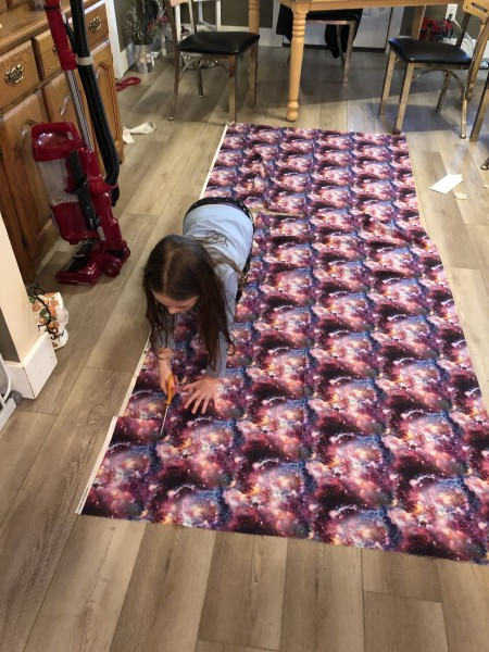 Lydia measuring and cutting fabric for the curtains in her room