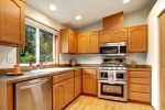 Kitchen overlooks green space and back yard