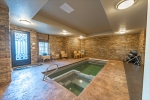 Indoor swim spa with attached home gym and sauna