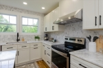 Tons of cabinets accented by marble backsplash