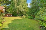 Private .28 acre lot features park like grounds