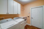 Laundry room with garage access and storage