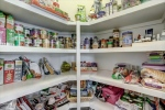 Walk-in corner pantry with solid shelving