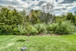 Back yard adjoins wooded area with trails
