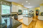 Cheery kitchen with white cabinets and granite