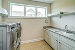 Large laundry room with cabinets and utility sink.