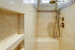 Walk-in shower with no glass includes bench