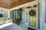 Cheery front door with storm door and transoms.