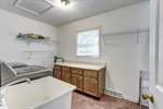 Laundry room features utility sink and cabinets