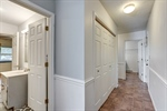 Hallway with storage leads to laundry and mudroom