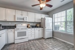 Large kitchen with white cabinets and granite