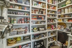 Walk-in pantry with pocket door and custom shelves