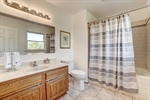 Spacious vanity and tile surround in shower.