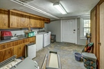 Basement laundry with utility sink and storage.