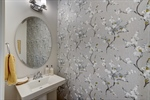 Powder room features beautiful wall covering.
