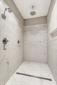Walk-in shower features dual shower heads.