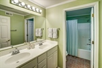 Full bathroom with double vanities in basement.