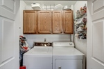 Laundry room in kitchen with storage cabinets!