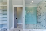 Stunning glass enclosed shower with unique tile.