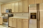 Kitchen features wood cabinets.
