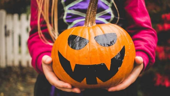 Child holding jack-o'-lantern for a safe halloween