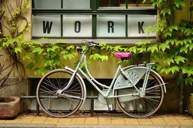 "parked bike in front of window that reads ""WORK."" Drive Less, Bike More."