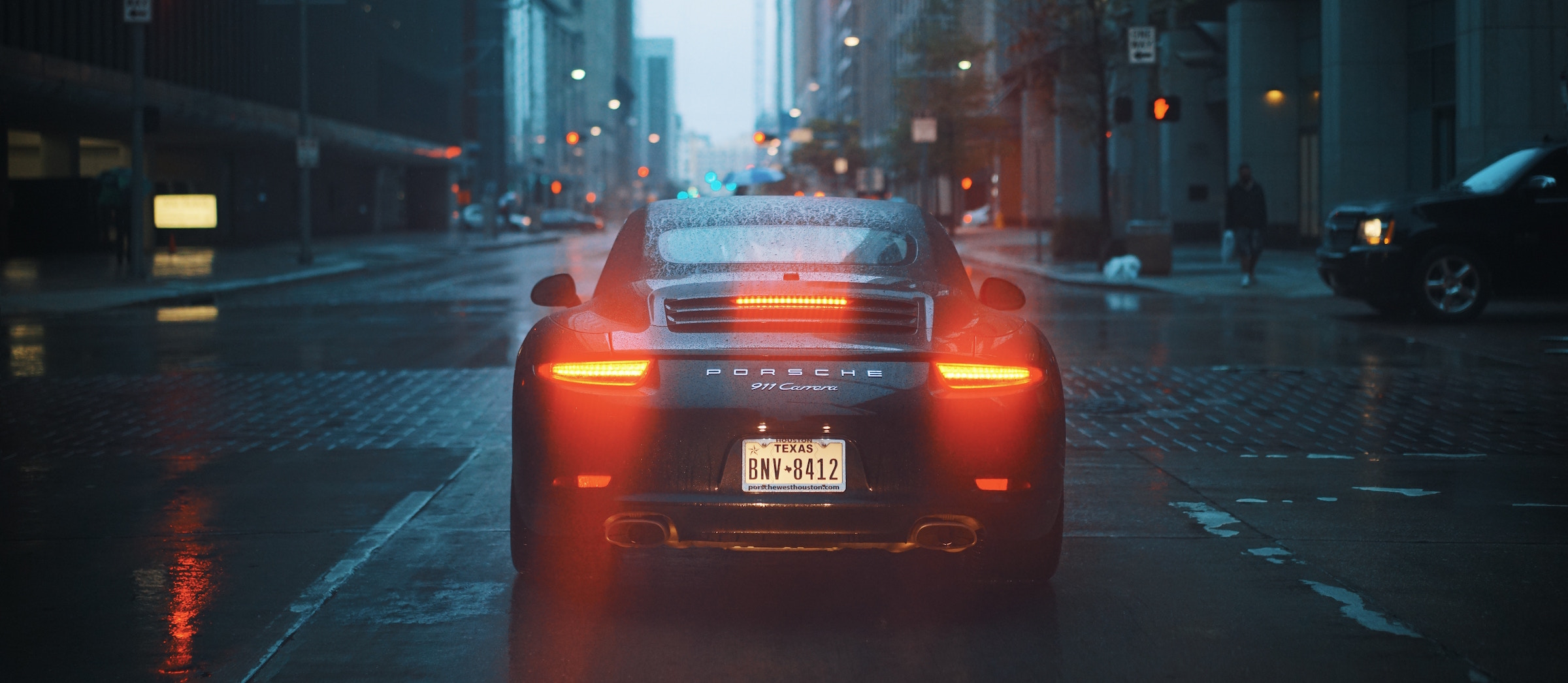 Porsche on rainy downtown road. OBD-II Port