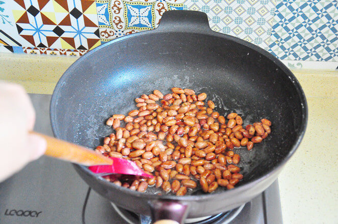 Peanuts are poured into the syrup