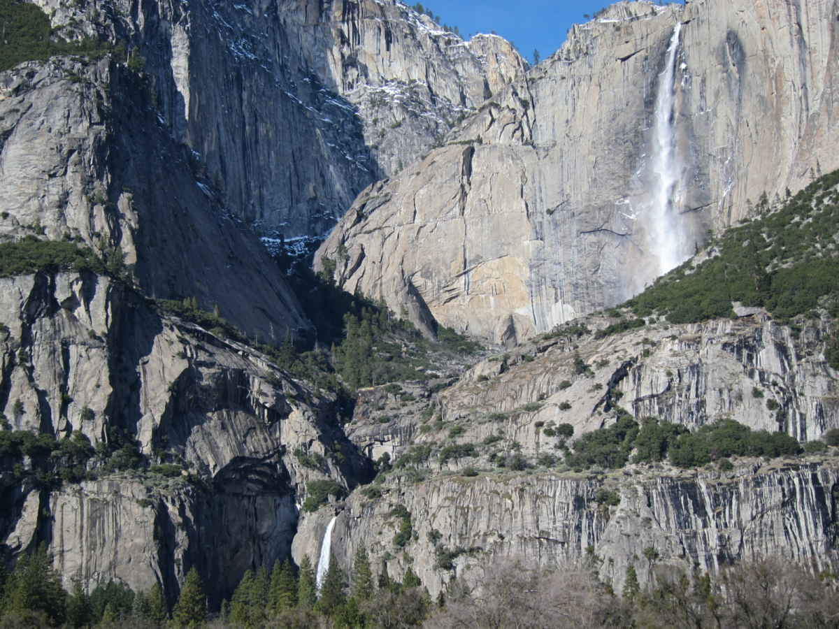 Water tumbles down in misty cascades over the vertical rock face, splashing off ledges and curves of rock. No one could survive the fall.