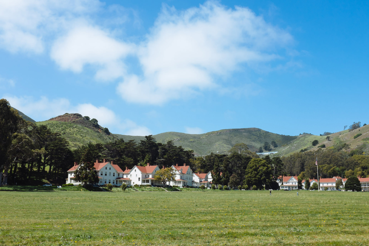 We pass a large green field, outlined in pretty white houses.