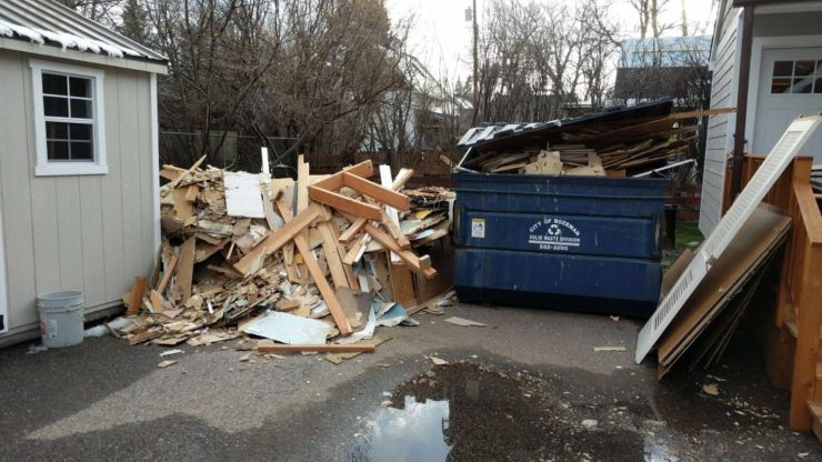 A pile of debris larger than the full dumpster sitting next to it.