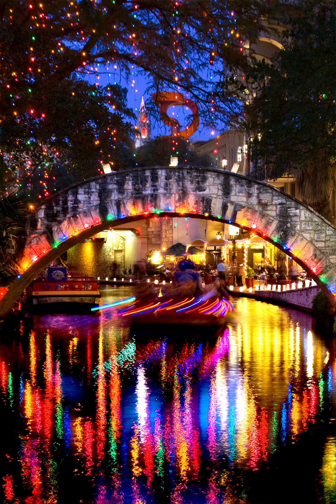 san antonio river walk christmas lights overhead and the luminarias lining the sidewalk