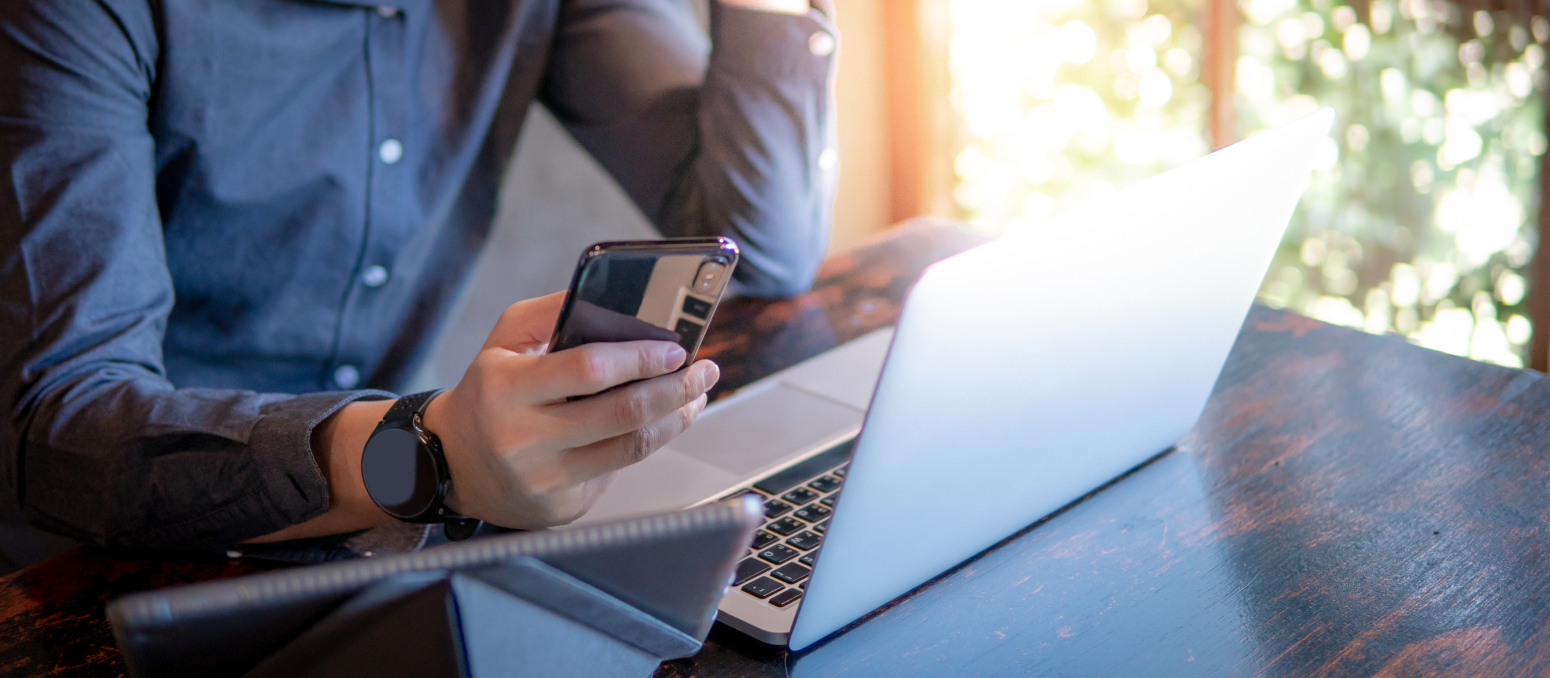 Man looking at phone with laptop