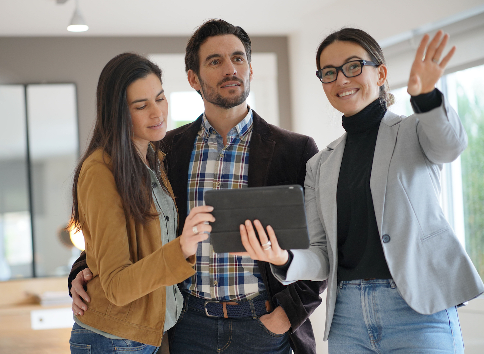 Real estate agent showing a property to a couple.