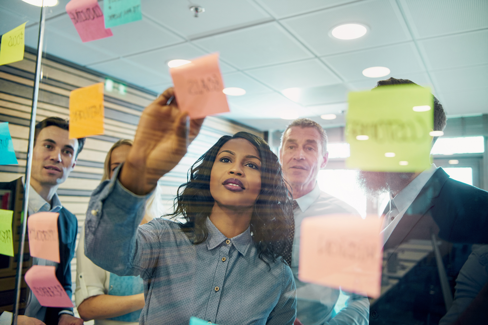 Young professional demonstrating strategy via post it notes.