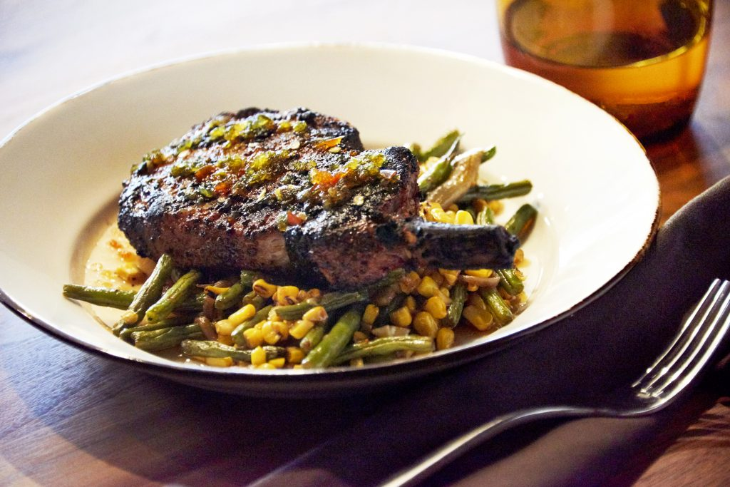 Coriander pork chop on vegetable bed Chef Stephan Pyles Stampede66 Allen