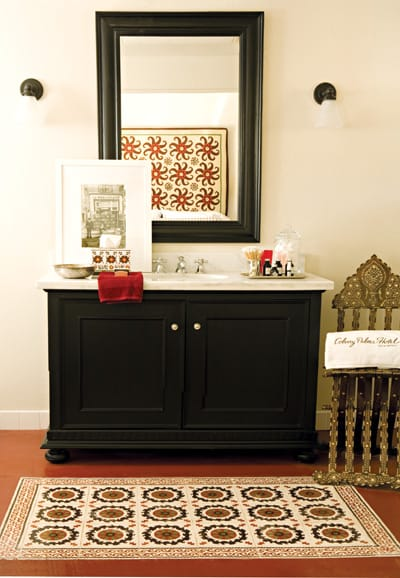 """Unsealed floor tile made in France comprises this """"carpet"""" in front of a bathroom sink."""