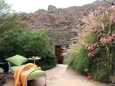 The Albert Frey rock house, which blends into the mountainside, was designed by the famed architect in the 1930s. The two-room house features walls of glass, a fireplace, Balinese garden doors, claw-foot tub, rock shower, granite polished sinks, concrete counters, and a meditation deck.
