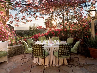 The rock-lined, bougainvillea-framed breakfast deck overlooks Palm Springs. Adjacent to the French countryside-styled kitchen, it is one of many outdoor living areas enjoyed by Suzanne Somers and Alan Hamel as a part of the lifestyle evoked by the expansive grounds.
