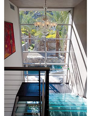 Jakway purchased the Venetian Murano glass chandelier in Florence. The glass sculpture standing below it came from Prague. A Vladimir Cora painting hangs to the left of the large window, which looks beyond the pool and patio to a rustic stone ruin.