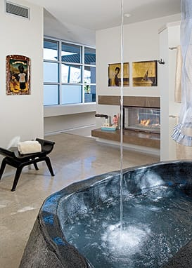 The black granite bathtub, polished inside, natural outside, and sculpted by Roger Hopkins of Desert Hot Springs, commands attention in the master bath; the Kohler tub filler directs a steady stream of water from the ceiling to the waiting tub below. Hopkins made a stone sink to match for the guest bath.