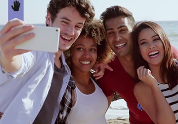 two couples at the beach taking a group selfie