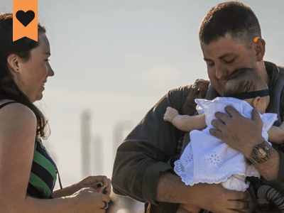us military man holding his baby with is wife standing to the left of him and the child facing them